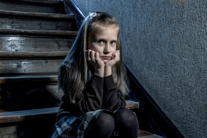 7 or 8 years old sad depressed and worried schoolgirl sitting on staircase desperate and scared suffering bullying and harassment at school