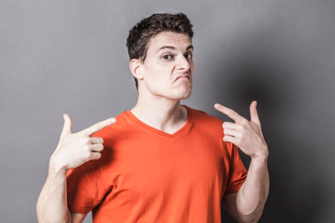 unhappy young sporty man showing throat with gun-like hands