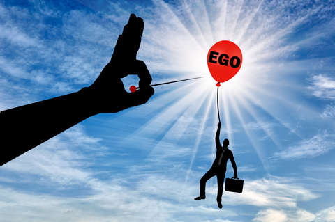 A selfish businessman clings to a balloon called the ego and a big hand with a needle intends to burst it