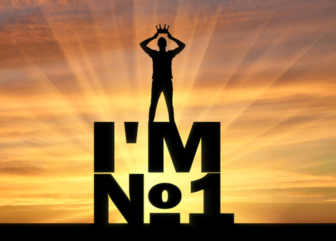Silhouette of a selfish and narcissistic man, he wears a crown, standing on a word, I'm number one